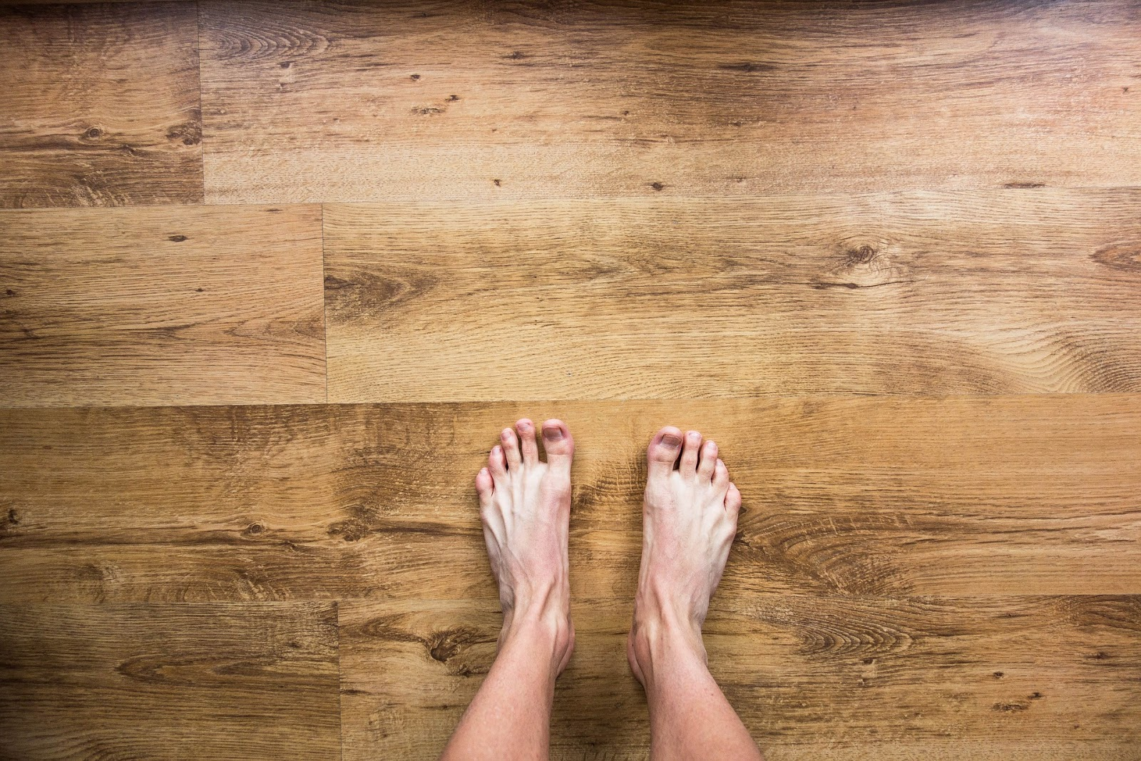 A pair of bare feet on a light-coloured wooden floor.
