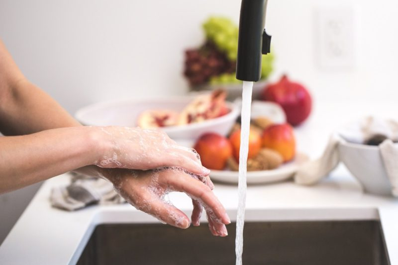 close-up of a pair of sudsy hands beside a running kitchen faucet.