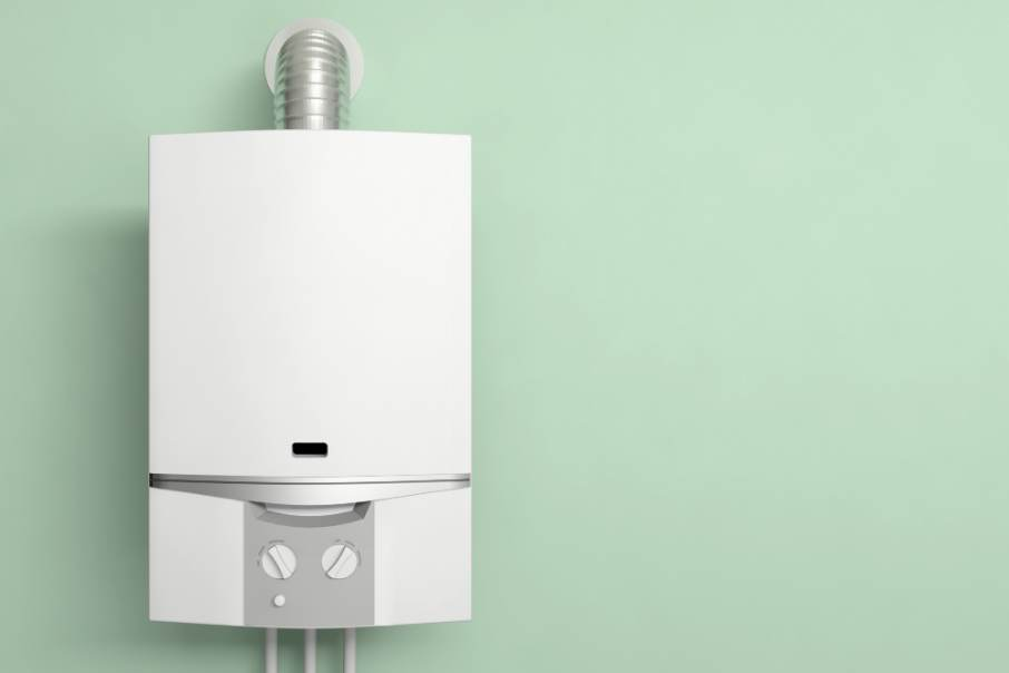 A white tankless water heater installed on a pastel green wall.