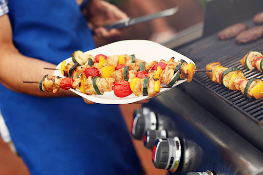 A person holding a plate of grilled kebabs next to a gas barbecue.